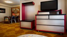 A TV atop a dresser and, beyond, a 'Cars'-themed table that turns into a double bed