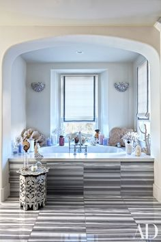 8. Increase your pattern play. Use a graphic motif to break up a monochromatic space, as Khloé did in the recessed alcove in her master bath. Ann Sacks striated marble flooring extends up the side of the tub, adding visual interest while echoing the cracked-mirror sconces beyond.