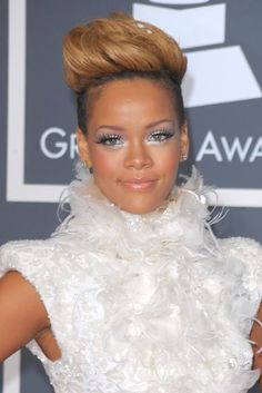 Rihanna with silver eye makeup, shaved head, swan feathers at the Grammy Awards in 2010.