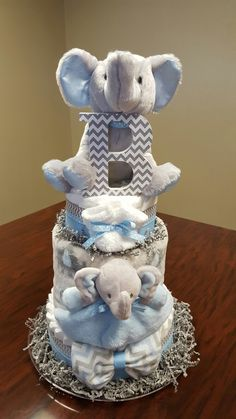 Elephants and baby blue, yep it's a boy! 3 tier diaper cake, baby shower gift.  Visit my Facebook page Simply Showers for more pics and orders.  https://m.facebook.com/adorablegifts