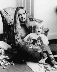 British model and actress Twiggy wears a turtleneck and leg warmers as she sits on the floor and holds her daughter Carly Lawson on her lap, Twickenham, England, 1983. Carly holds a small child's book and there are toy dinosaurs and a pack of Carlton cigarettes on the floor beside the pair.