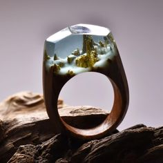 Canadian jeweler Secret Wood's resin rings not only boasts originality in each handmade ring but it also wins our stamp of approval in the unique accessory category. Literally giving you something poetic to stare at, each bauble reveals a one-of-a-kind contained landscape from a group of snow-capped mountains to a desolate terrain filled with fallen trees. Made with fresh wood and jewelry resin, minuscule air bubbles add a mystifying touch to each magical scene giving its wearer a truly ...