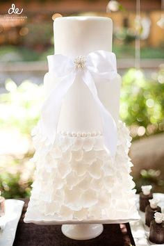 Beautiful white wedding cake with petal base layer and a bow accent.