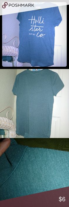 Hollister Tee Gently used Hollister teal colored shirt with silver embroidery. No longer fits. Hads a pilling in some spots (as pictured) and super tiny hole under the right sleeve (already there when I purchased it, not noticeable)   Still looks great! ? Hollister Tops Tees - Short Sleeve