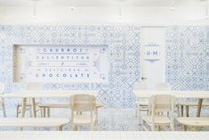 Chocolate and churro cafe,  EL MORO, which is covered in white tiles with blue graphics, was designed by Cadena + Asociados. The mosaic of blue motifs express the brand's personality, and the white was apparently inspired by sugar. See how using simple graphic tiles can have a powerful design impact. Photography by Moritz Bernoully