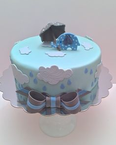 Cakesbykirsten.  Baby shower theme cake with raindrops, clouds, sugar umbrella and elephant. #babyshowergrayblue #elephant #raindropsumbrella