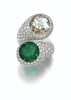 EMERALD AND DIAMOND RING Of cross over design, set with a circular-cut emerald and a rose-cut diamond of brownish tint, on a mount pavé-set with brilliant-cut diamonds