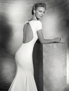 Vestido de sencillo de novia de crepe de estilo sirena de manga corta. Cuerpo de escote barco en el delantero y gran obertura central en la espalda.