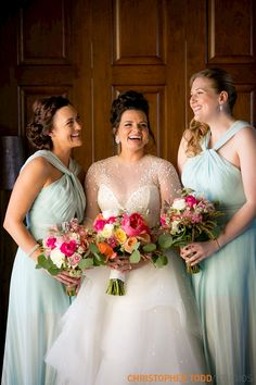 bride with bridesmaids in Halston gowns laughing