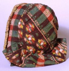 1850    Child's bonnet made from dark printed cottons, lightly padded with wool and hand-quilted. The brim is faced with pink and green check silk