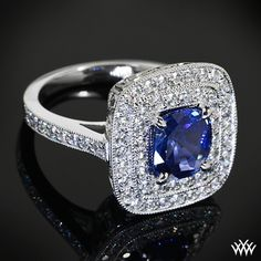 This gorgeous Double Halo Diamond Engagement Ring features a 1.00ct Cushion Cut Blue Sapphire center stone.  Surrounded by 0.68ctw A CUT ABOVE® Hearts and Arrows Diamond Melee and topped off with milgrain edging.