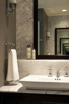Nice herringbone design and marble shelf behind sink. Sconce on alternate wall. Master bath remodel.