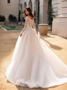 Special Order - Allow 4-6 months. This long-sleeved, off-the-shoulder, lace ballgown is sampled in a bridal size 20, in the color pictured. Available to order in sizes 2-28, in ivory/taupe, or all ivory.