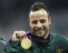 Oscar Pistorius shows off his gold medal and celebrates his win