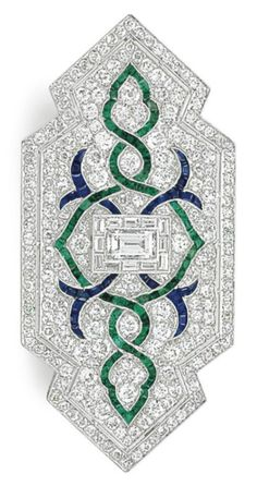 AN ART DECO DIAMOND, EMERALD AND SAPPHIRE BROOCH, CIRCA 1925. Centring upon a rectangular-cut diamond, within a baguette-cut diamond surround, to the intertwining calibré-cut emerald and sapphire motif, on a ground of single and old-cut diamonds, completed by a single-cut diamond border, 2 5/8 ins., mounted in platinum, with pendant hoop for suspension. #ArtDeco #brooch #pendant