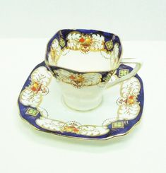 Items similar to Standard China Stuart Shape tea cup saucer set with cobalt blue and gold trim green clovers in golden diamonds - Reg number 768534 on Etsy
