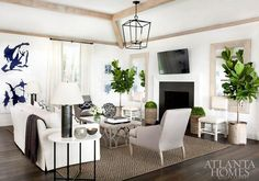 White and gray living room features wood beams over a white slipcovered sofa flanked by round black and white end tables and black industrial lamps facing a gray coffee table and a pair of gray accent chairs atop a brown diamond pattern jute rug.