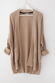 """- Tan chunky knitted cardigan with an open front - Large patched front pockets - Long sleeves - Dropped shoulder and a loose fit - Size small measures approx. 30"""" in length - 60% Cotton 40% Acrylic -"""