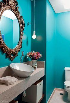 """O arquiteto Paulo Alves renovou o visual deste ambiente com poucos elementos, como o tom azul-esverdeado das paredes (Anil Tintas, ref. SW-6947*), o espelho com moldura antiga, o pendente (Reka) e a prateleira de madeira sob a bancada original de mármore travertino. """"Áreas pequenas, como esta, de 2,50 x 1,30 m, parecem maiores ao ganhar uma cor inesperada, que prende o olhar e afasta as paredes para longe"""", afrma."""