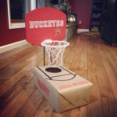Basketball/Ohio State Buckeyes Valentine box.  Covered shoe box in craft paper.  Used Cricut to cut letters using the varsity font.  Covered a hoop found at Target with cardstock.  Hot glued two dowel rods to the back of the board.