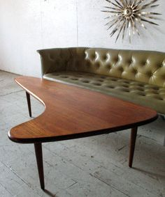 Boomerang coffee table and olive green couch.