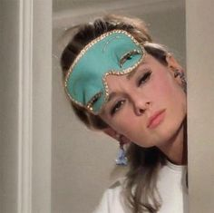 Audrey Hepburn wearing her Tiffany Blue colored sleeping mask and fringed ear plugs answers the door to meet her new neighbor in a scene from 'Breakfast at Tiffany's' (1961).