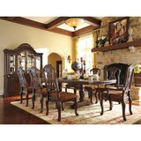 Ashley North Shore RECT DRM DBL Pedestal EXT Table Set - A deep rich stained finish and exquisite details come together to create the ultimate in grand traditional design with the elegance of the North Shore dining room collection. The opulent brown stained finish flows beautifully over the decorative pilasters and ornate detailed appliques to create a rich elegant atmosphere to any dining experience. With the comfort and beauty of elegantly upholstered chairs, this furniture collection ...