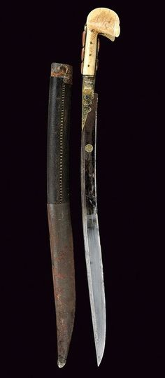 Ottoman yatagan, 19th century, typical, slightly curved, single-edged blade with double rear groove, blued at the first part, with a round, gold cartouche with Arabic inscription, and decorations with inscriptions in gold. It has a gilt copper hilt, decorated with filigree and large cabochon corals and glasses. The walrus ivory grip scales features the typical large 'ears', while the wooden scabbard is covered in leather and has simple iron mounts. overall length 75 cm.