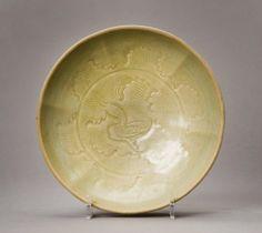 A Yaozhou celadon lobed bowl, Jin Dynasty, moulded with a duck amongst waves, under an olive-green glaze 17cm diameter