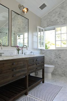 The rustic wood vanity is a striking contrast to the extravagant carrara marble floor and wall tile in this stunning spa bath.