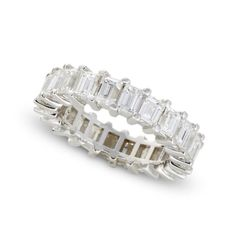 A diamond and eighteen karat white gold eternity band <br /> set with rectangular step-cut diamonds; estimated total diamond weight: 4.90 carats. <br /> <br /> Ring size: 7 <br />