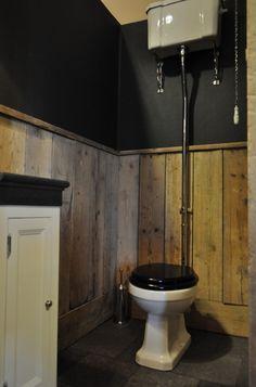 Traditional toilet met hooghangend reservoir. Wanden met steigerhout lambrisering. Vloer in basalt tegels