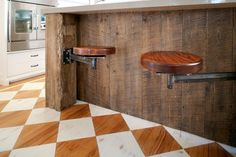 This reclaimed wood kitchen island lends a rustic vibe to the space, which also features white diamond painted hardwood flooring. To save space, the wooden barstools were custom built to fold under the bar when not in use.