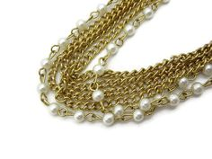 A vintage costume jewelry multi strand long chain necklace, in gold tone metal with faux pearls. The faux pearl strand is removable, for a
