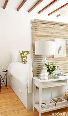 Fitzhugh Karol and Lyndsay Caleo of The Brooklyn Home Company put a rustic wooden room divider at the foot of the IKEA Brimnes bed to create privacy and define the sleeping area in this...