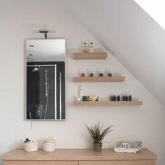 Making a feature out of a sloping roof in an attic bathroom with floating shelves. Not just for bathroom