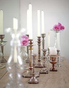 Além de iluminar a mesa, a coleção de castiçais diferentes decora o ambiente
