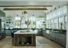 Wood beams run across a vaulted shiplap ceiling accented with three Antique Brass Hicks Pendants hanging over a dark stained oak kitchen island topped with Danby Marble lined with blue leather counter stools and fitted with built-in dog food and water bowls.
