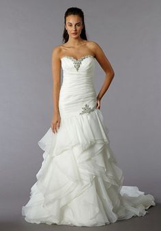 Sweetheart A-Line Gown in Organza. This a-line gown features a sweetheart neckline with a dropped waist in organza and beaded embroidery. It has a chapel train. This gown is Exclusive to Kleinfeld Bri