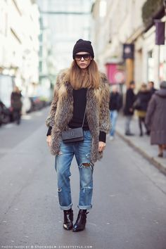 Evangelie in ripped boyfriend jeans, coyote fur coat, black knit cap, CHANEL crossbody, and black ankle boots.
