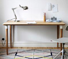 Valkoista seinää vasten puinen työpöytä, jonka päällä metallinen pöytävalaisin.