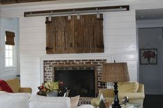 Reclaimed barn doors used to conceal TV over fireplace.  Track from Tractor Supply.
