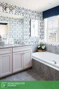 A beautiful tile bathtub surround and gray tile flooring work in harmony with the dark granite countertop in the Hadden model's master bathroom. A navy-blue valance that hangs over a pair of double-hung windows matches the room's blue trellis pattern wallpaper. White sand decor by the sink and white orchids by the spa tub make this a dream bathroom. #InteriorDesign