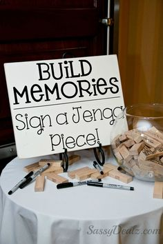 DIY Jenga guestbook wedding idea! The sign Build memories sign a jenga piece was made from a wood board with decal letters. Just buy the jenga game and spread the wood pieces out on the table. Buy 5-7 thin point black sharpies so your guests can write on them. Buy a big fish bowl for them to put the jenga blocks in when they were done. Lots of compliments!