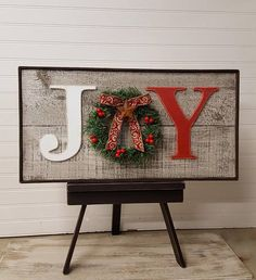 Rustic barn wood look Joy sign has a decorated wreath in place of the O. Very country with the rough sawn wood painted to look like weathered barn wood and a rusty tin star hanging from the bow on the wreath. The bow and decorations on the wreath varies in design and color by whats available to me, but it will always match beautifully. Backs are left natural with slotted hangers on the back for easy display. This would look great on the mantle or hanging by the Christmas tree! Its the…
