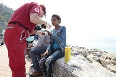 Eine italienische Rote-Kreuz Mitarbeiterin bei der Versorgung von Flüchtlinge.