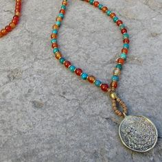 Carnelian and turquoise 108 bead mala necklace, stringed on stainless steel thread for increased durability, and a counter every 27 beads, with a beautiful hand made brass pendant of a Tibetan calenda