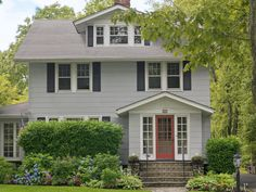 "Linda and Bill Bradley purchased their 1920s home in 2000. ""We can't take credit for the red door, but it's one of the things we love most about the house, along with all of the flowers in front."""