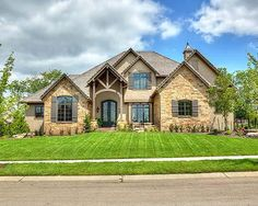 Summer Lake floor plan front exterior view with stucco and stone exterior finishes and featuring wood beams. Stucco And Stone Exterior, Brick Exteriors, House Exteriors, Aka House, Southern Living House Plans, Brick Colors, House Elevation, Front Elevation, Stone Houses