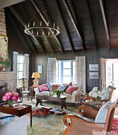 Designer Rhoda Burley Payne lightened the heaviness of this Missouri cottage's dark interior with soft blue-and-ivory fabrics and creamy sofas. The sofas are covered in Donghia's outdoor fabric, Pinata. Curtains are Vervain's Blythe. The armchairs are from Century Furniture. The rug is by RugStudio. See more comfortable rooms.   - HouseBeautiful.com